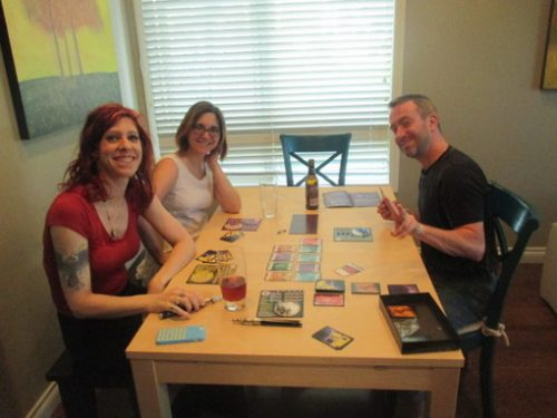 Chris (left), Jessica (rear left), Simon (right) smiling as they destroy the world with plague.